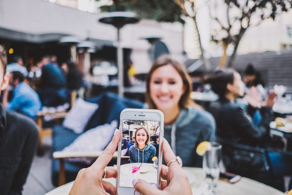 Hands holding an iPhone being used to take a photo of a woman sitting across the table
