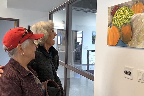 Two older women look at a painting by Aurora Hernandez